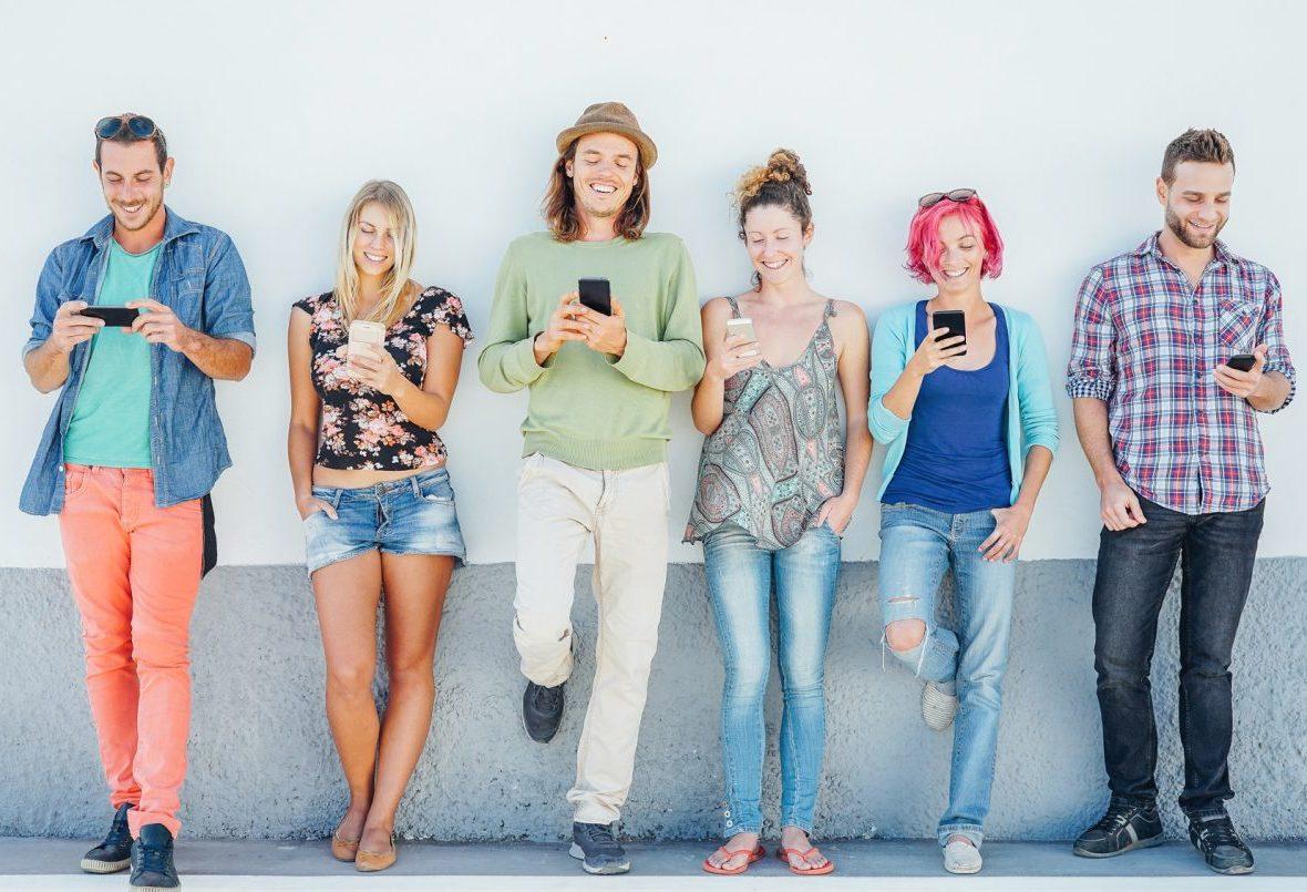 Jovens prestam atenção em seus telefones móveis espertos que inclinam-se em uma parede - geração viciada à tecnologia nova - conceito do apego da juventude às tendências sociais da rede