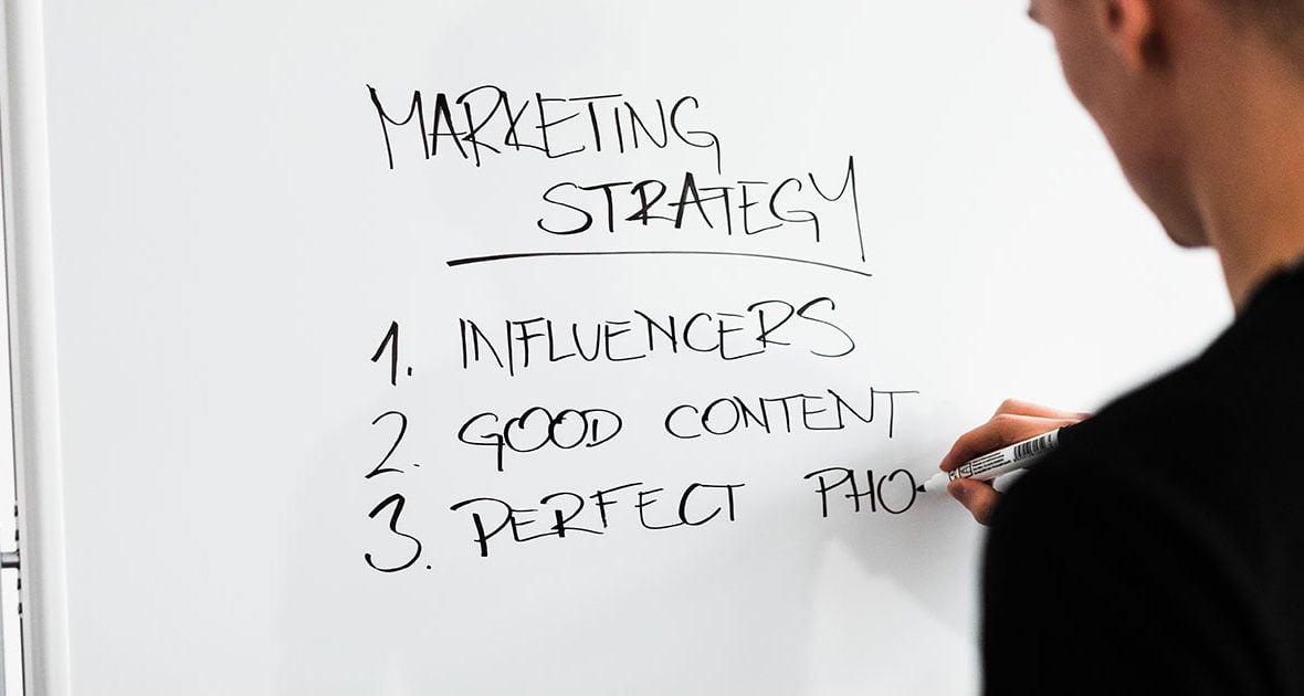 homem escreve marketing strategy num quadro branco