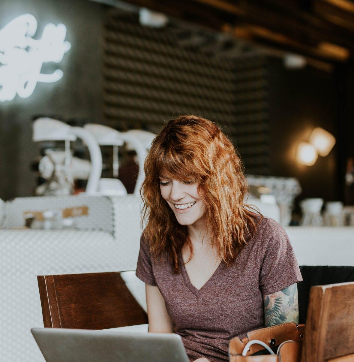 mulher a sorrir em frente a um mac