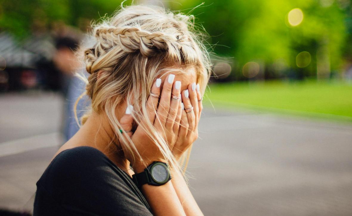 mulher loira com maos na cara implicando desilusao
