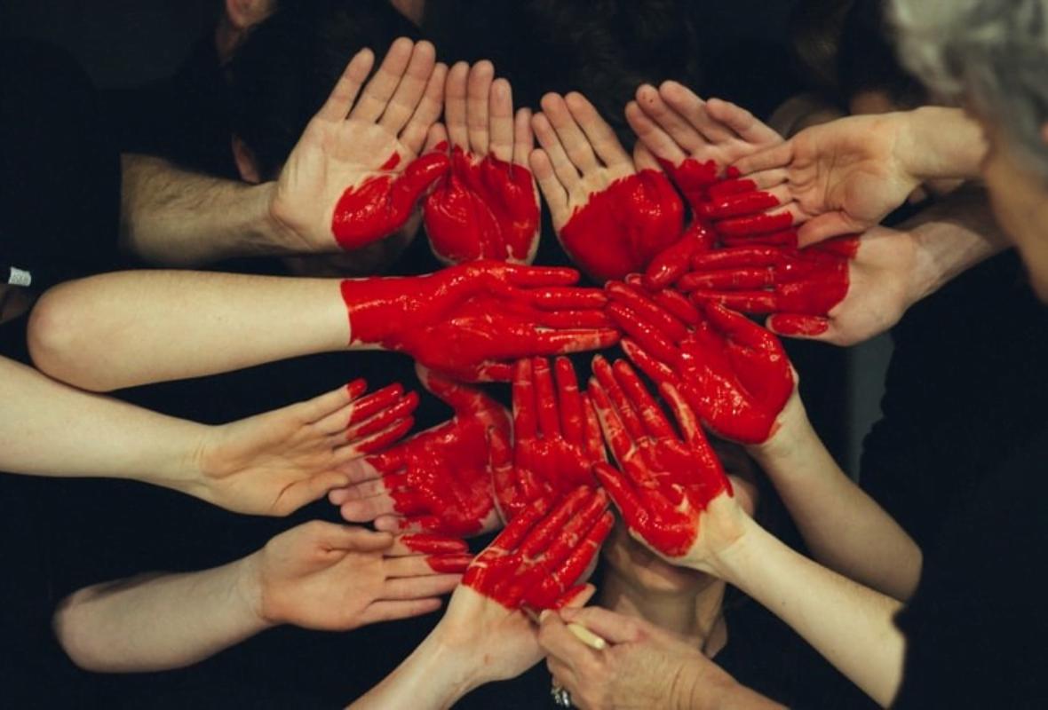 Várias mãos juntas pintadas de vermelhos a formar um coração