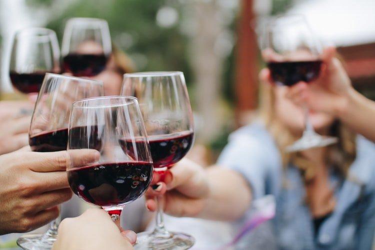pessoas a brindar com vinho tinto