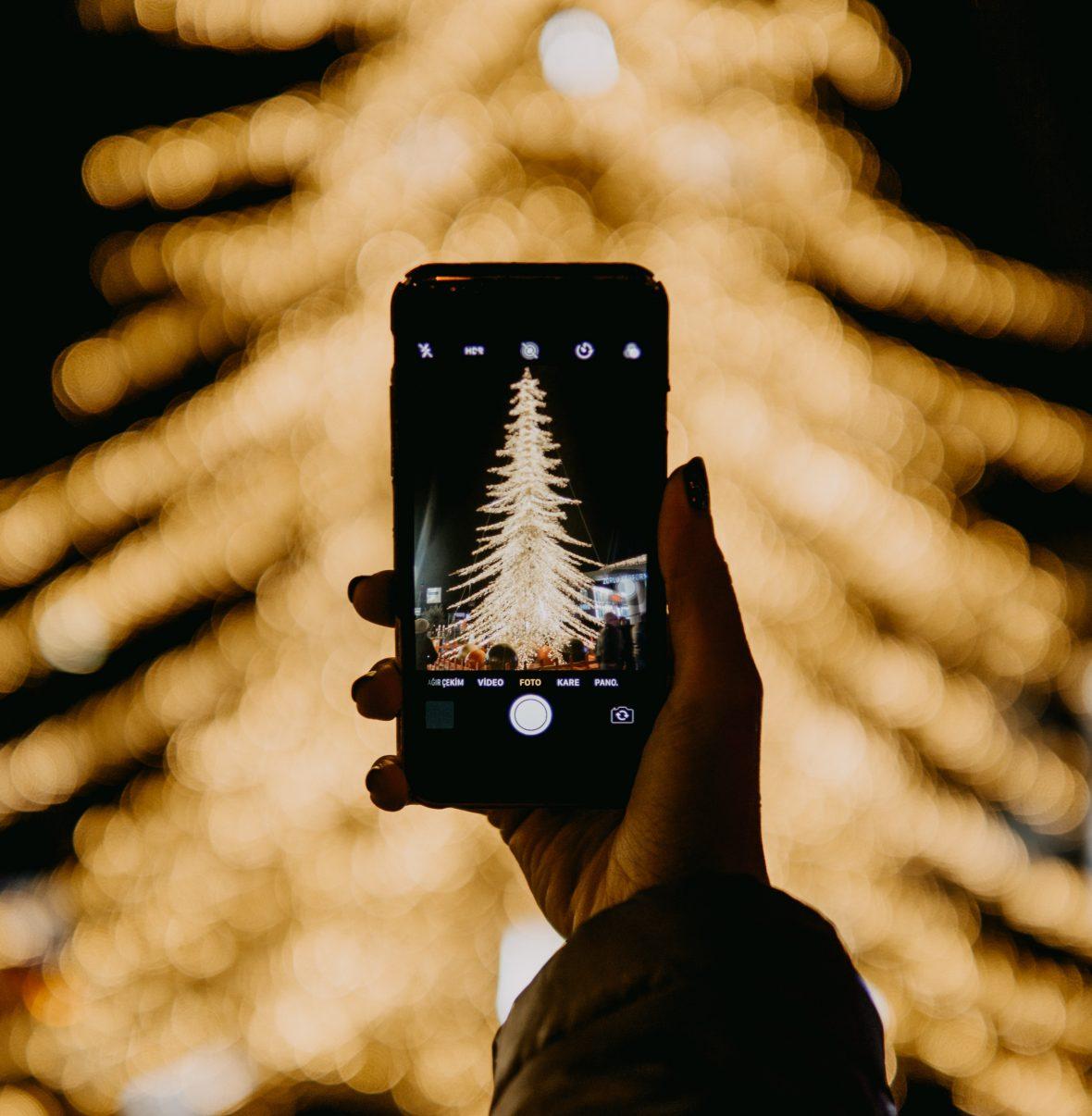 Pessoa a tirar uma foto a uma árvore Natalícia