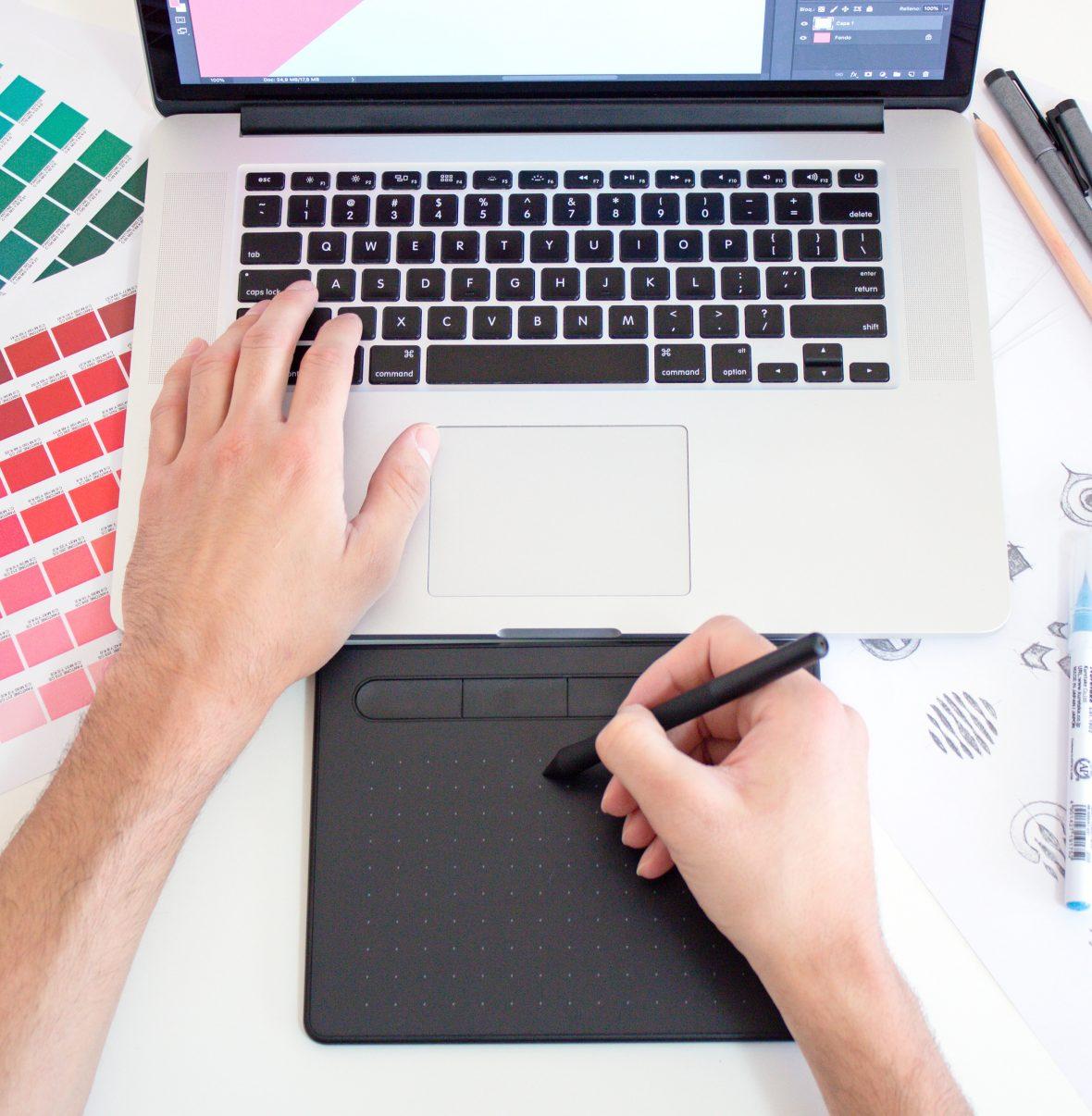 pessoa a utilizar um computador com materiais de design À sua volta